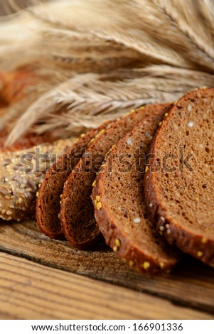different pastries and bread with ears of rye and wheat on the wooden background - stock photo