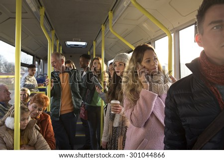 Different people can be seen traveling on the bus. Some are talking to other people, others are using technology or looking out the window.   - stock photo