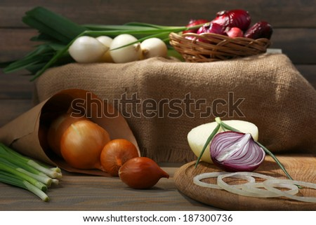 Different raw onion on wooden background - stock photo
