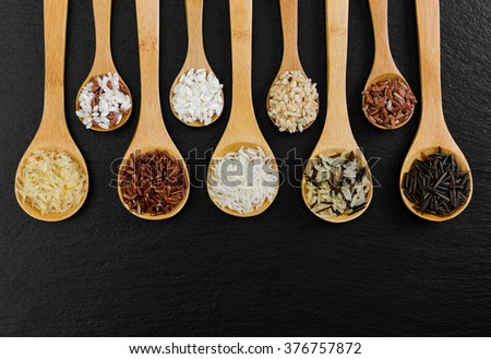 Different rice in spoons on black background
