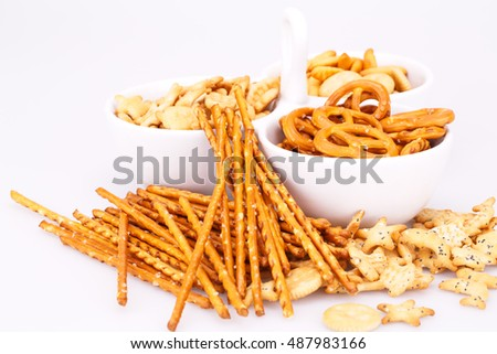 Different salted crackers in bowl isolated on white background.