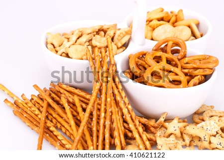 Different salted crackers in bowl on white background. - stock photo