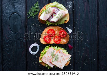 Different sandwiches with meat and vegetables on a black background - stock photo