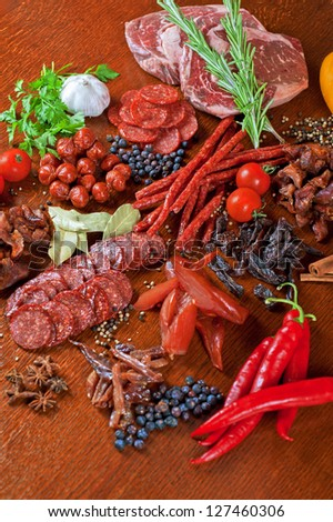 different sausage and meat on a celebratory table with spices and vegetables - stock photo