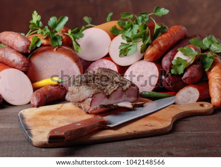 Different sausages and smoked meats on a old wooden table .