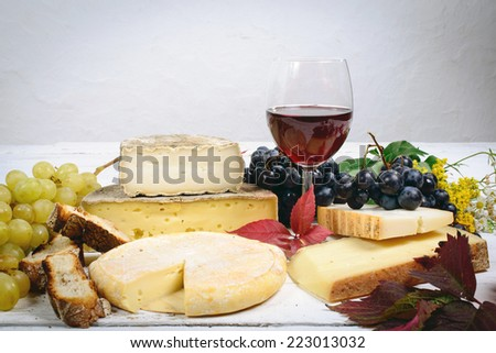 different Savoie cheeses with a glass of red wine