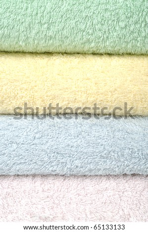 Different shades of  towels stacked on each other on a white background - stock photo