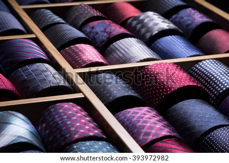 Different silk neckties packed on shelves in a store