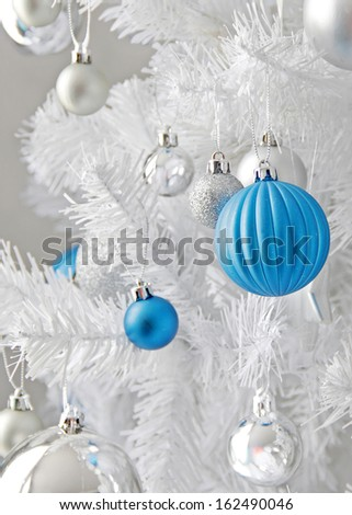 Different sizes and texture Christmas ball hanging on a white christmas tree.