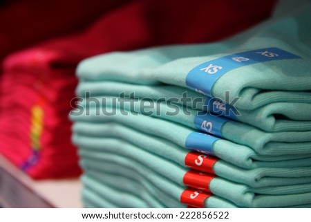 Different sizes of clothes in the shop - stock photo