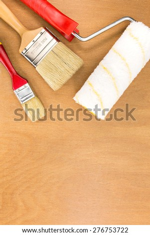 different sizes of paintbrushes with paint roller on wooden background - stock photo