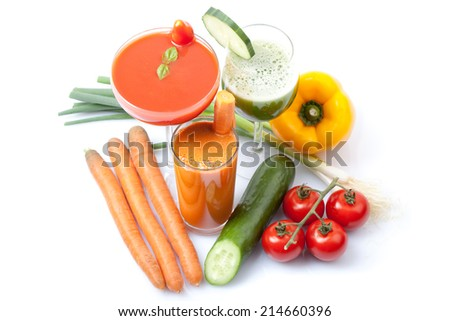 Different smoothies and juices of tomato, cucumber and carrots, surrounded by vegetables, white background, isolated, aerial perspective - stock photo