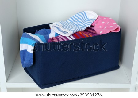 Different socks in textile box on closet background - stock photo