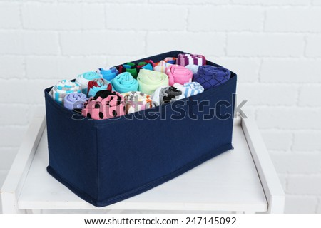 Different socks in textile box on shelf and white brick wall background - stock photo