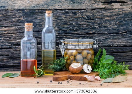 Different sorts of cooking oil,olive oil flavored and Sesame oil with spices herb rosemary ,thyme,dill,sage and parsley set up with old wooden background. - stock photo