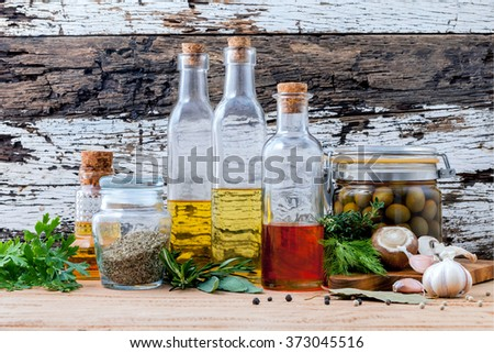 Different sorts of cooking oil,olive oil flavored and Sesame oil with spices herb rosemary ,thyme,dill,sage and parsley set up with old wooden background.