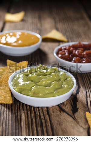 Different sorts of Nacho Dips (soft focus) on wooden background - stock photo