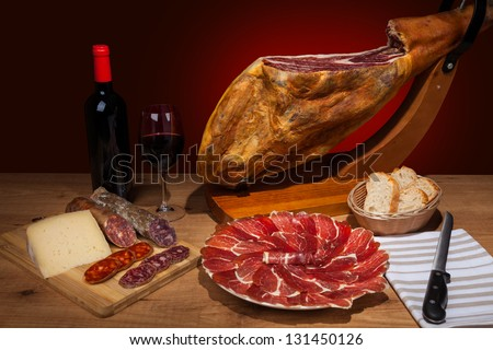 Different spanish embutidos on a table: jamon, chorizo, salami, cheese and a bottle of wine - stock photo