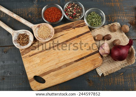 Different spices and herbs with cutting board on color wooden table background - stock photo