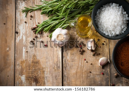 Different spices, rosemary, allspice, garlic, oil and salt on a wooden board, rustic kitchen background - stock photo
