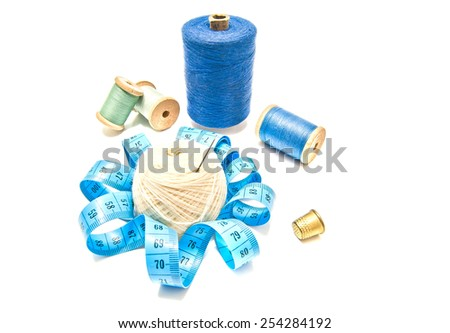 different spools of thread and yarn on white background - stock photo