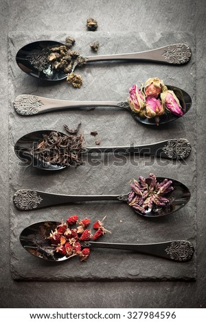 Different tea and dried herbs in vintage spoon. Top view, vertical