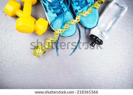 Different tools for sport on grey background - stock photo