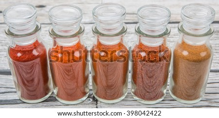 Different type and colors of chilly powder, paprika powder, cayenne powder in glass vial over wooden background