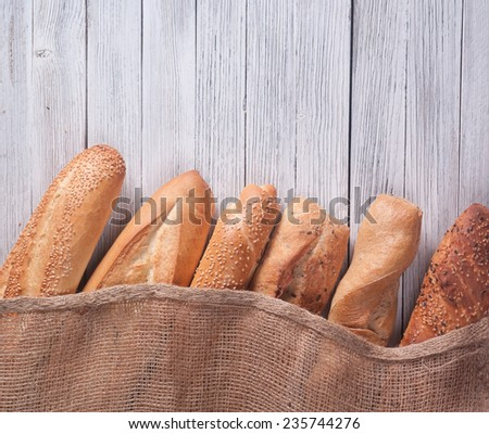 different types of baguette on a wooden background - stock photo