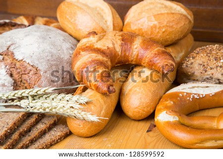 Different types of bakery products such a a loaf of bread, pretzel, whole grain bread and buns
