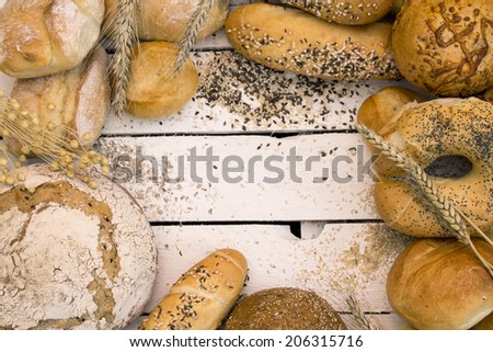 Different types of bread on white wooden board - stock photo