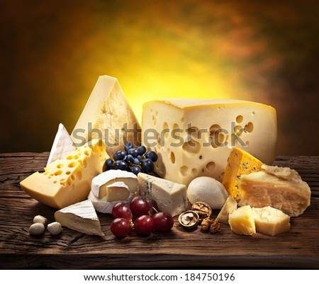 Different types of cheese over old wooden table. - stock photo