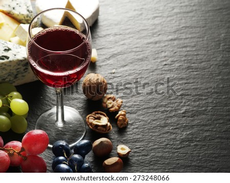 Different types of cheeses with wine glass and fruits.  - stock photo