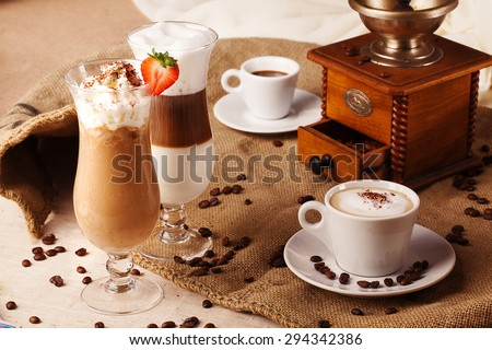different types of coffee in the glass and cups with whipped cream and strawberries in a still life with coffee grinder and beans with burlap - stock photo