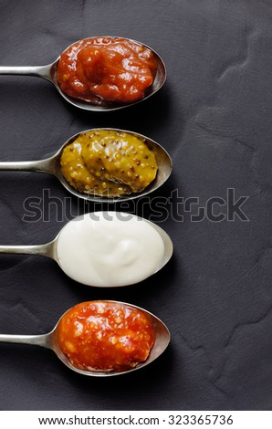 DIfferent types of condiments on vintage spoons on slate background, mayonnaise, tomato sauce, mustard and sweet chilli jam