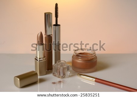 Different types of cosmetics in goldish color on warm background. Shallow DOF (lipstick, sparklets, front of jar). - stock photo