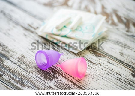 Different types of feminine hygiene products - menstrual cups, sanitary pads and tampons. Selective focus and shallow DOF - stock photo