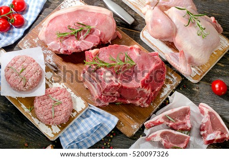Different types of fresh raw meat with vegetables and herbs on dark wooden background. Top view