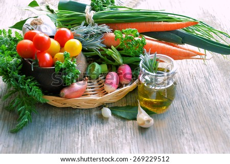 different types of fresh vegetables, carrots, tomatoes, cabbage, zucchini, herbs and olive oil in a basket - stock photo