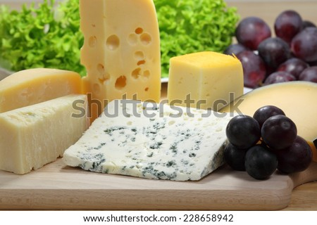Different types of hard and mold cheeses on a wooden board. - stock photo