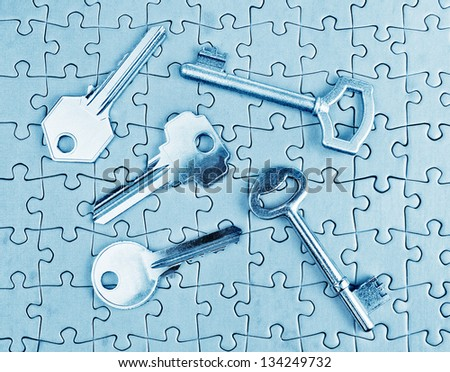 Different types of keys on the puzzle close-up in cold tones. - stock photo