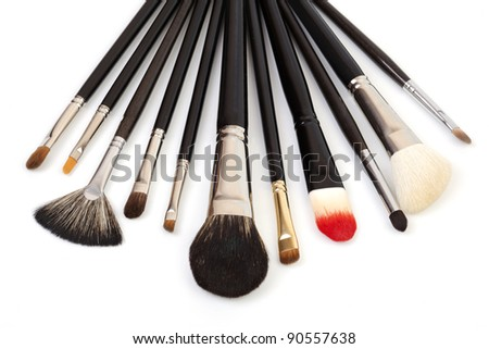 Different types of makeup brushes on white background