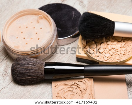 Different types of makeup cosmetic products to even out skin tone and complexion with brushes on shabby wooden surface. Cream-to-powder foundation, compact powder, jar of loose powder