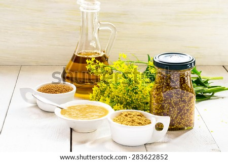 Different types of mustard: powder, seeds, cooked Dijon mustard, spicy Russian mustard, mustard oil, mustard flowers on a white wooden table. Selective focus - stock photo