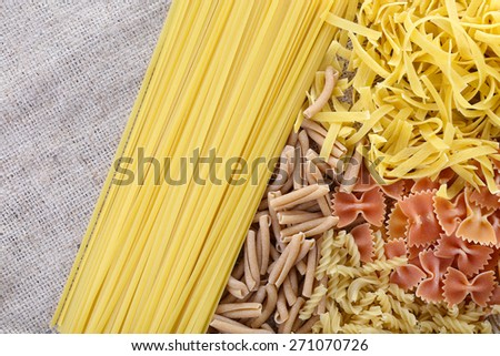 Different types of pasta on sackcloth background - stock photo