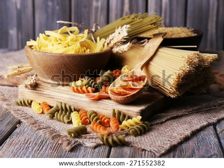 Different types of pasta on sackcloth on wooden background - stock photo