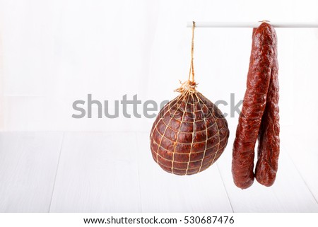 Different types of smoked salami sausages on white. Copy space