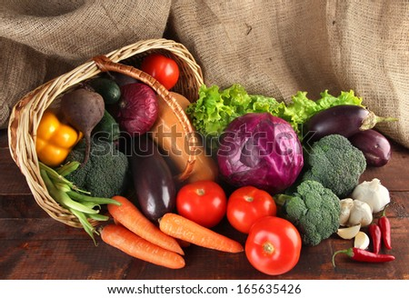 Different vegetables in basket on table on sackcloth background - stock photo