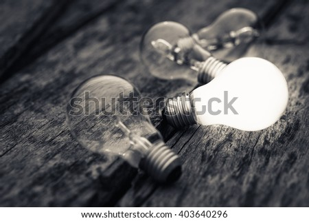 Different white light bulb glowing on wood background - stock photo