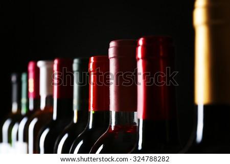 different wine bottlenecks on dark background - stock photo